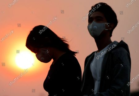 A couple with masks walk during the sunset in Yangon, Myanmar, 08 May 2020.