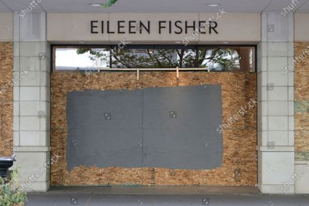 An Eileen Fisher clothing store is shown boarded up and closed in downtown Seattle. Nearly all retail stores and restaurants in the area are currently closed or operating under reduced levels of service due to the outbreak of the coronavirus and state-wide stay-at-home orders, which has led to thousands of workers losing their jobs or being furloughed