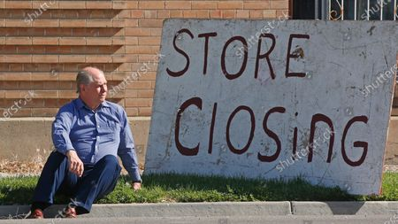 """Euro Treasures Antiques owner Scott Evans poses next to his """"store closing"""" sign, in Salt Lake City. Evans is closing his art and antique store after 40 years, though this year started out well for his business, then COVID-19 hit, along with shelter-in-place orders. The U.S. unemployment rate hit 14.7% in April, the highest rate since the Great Depression, as 20.5 million jobs vanished in the worst monthly loss on record"""