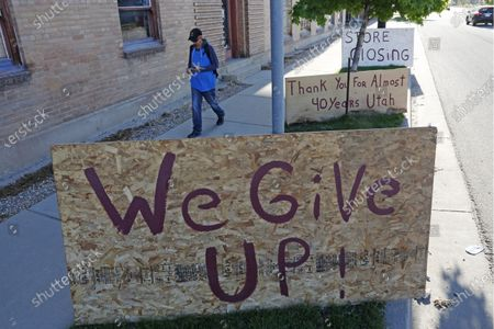 """Man walks past a """"we give up"""" sign outside Euro Treasures Antiques, in Salt Lake City. Scott Evans is closing his art and antique store after 40 years. This year started out well for his business, then COVID-19 hit, along with shelter-in-place orders. With a drastic drop in customers, Evans says it was no longer cost effective to stay open. The U.S. unemployment rate hit 14.7% in April, the highest rate since the Great Depression, as 20.5 million jobs vanished in the worst monthly loss on record"""