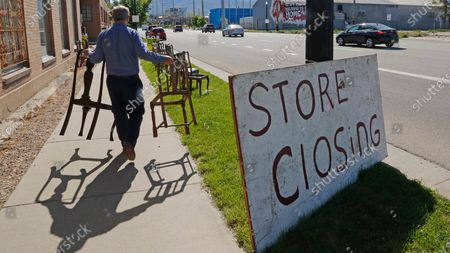 Stock Image of Euro Treasures Antiques owner Scott Evans carries chairs, in Salt Lake City. Evans is closing his art and antique store after 40 years. With a drastic drop in customers due to COVID-19 concerns and shelter-in-place orders, Evans says it was no longer cost effective to stay open