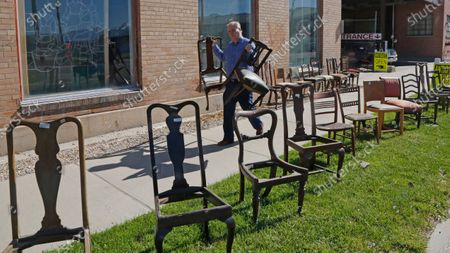 Euro Treasures Antiques owner Scott Evans carries chairs, in Salt Lake City. Evans is closing his art and antique store after 40 years. With a drastic drop in customers due to COVID-19 concerns and shelter-in-place orders, Evans says it was no longer cost effective to stay open