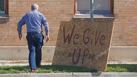 """Stock Photo of Euro Treasures Antiques owner Scott Evans walks past a """"we give up"""" sign, in Salt Lake City. Evans is closing his art and antique store after 40 years. With a drastic drop in customers due to COVID-19 concerns and shelter-in-place orders, Evans says it was no longer cost effective to stay open"""