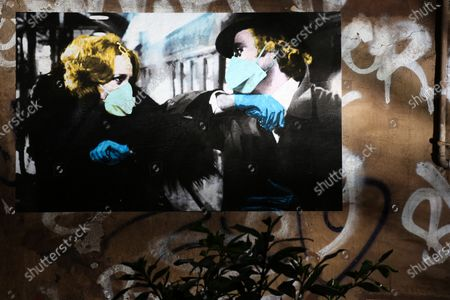 """Stock Image of A street poster art by artist Harrygreb in Trastevere neighborhood in Rome representing the Young Frankenstein movie characters Dr. Frederick Frankenstein ( Gene Wilder ) and Elizabeth (Madeline Kahn ) wearing masks while exchanging the """"taffeta darling"""" greet, that is also the name of the artpiece"""