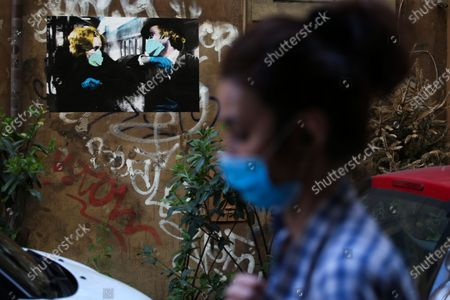 """Stock Photo of A woman that wears a mask walks in front of a street poster art by artist Harrygreb in Trastevere in Rome representing  the Young Frankenstein movie characters Dr. Frederick Frankenstein ( Gene Wilder ) and Elizabeth (Madeline Kahn ) wearing masks while exchanging the """"taffeta darling"""" greet, that is also the name of the artpiece"""