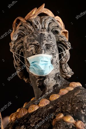Statue of the Trocadero's fountain wears a mask during nationwide confinement measures to counter the Covid-19, in Paris, . France continues to be under an extended stay-at-home order until May 11 in an attempt to slow the spread of the COVID-19 pandemic