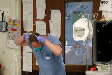Registered nurse David Morgan pulls on a face mask as he prepares to enter a patient's room in the COVID-19 Intensive Care Unit at Harborview Medical Center, in Seattle. Data from COVID-19 projection models show that the rate of infection is increasing in Washington state, Gov. Jay Inslee said Friday, as he urged people to follow his measured approach to slowly reopening the state from his stay-at-home restrictions