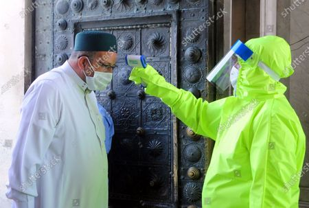 A staff member checks body temperature of a man before he enters a mosque in Damascus, capital of Syria, on May 8, 2020.   Mosques in Syria reopened on Friday for the first time since March as part of the government's plan to ease the measures against the COVID-19 pandemic.