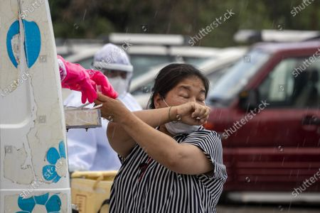 Woman sneezes as a doctor prepares to take a nasal swab to be tested for the coronavirus in Dharmsala, India, . India relaxed some coronavirus lockdown restrictions on Monday even as the pace of infection picked up and reopenings drew crowds of people