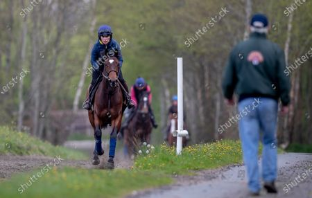 Katie Walsh rides out on a two year old colt by Territories out of Miss Raven watched by her father Ted Walsh