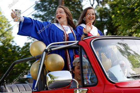 Jenna Swiney, top left, and Mary Grace Young, top right, wave from their vehicle as they participate in a neighborhood parade honoring 2020 student graduates from both J.J. Pearce and Richardson High Schools in Richardson, Texas, . The event was organized by a group of parents who asked neighborhood residents to come out and cheer on the local graduates who's traditional ceremonies were cancelled due to COVID-19