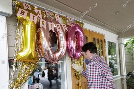 David Steele waves to his grandmother, Rhoda Kay, from behind a window at Aegis Living San Francisco, as no visitors are allowed inside the the senior living facility during the coronavirus outbreak, in South San Francisco, Calif., . Kay was celebrating her 100th birthday