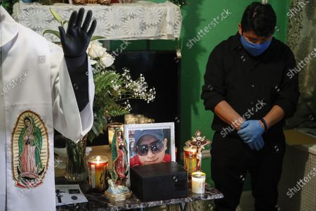 The Rev. Fabian Arias, left, performs an in-home service beside the remains of Raul Luis Lopez who died from COVID-19 the previous month as Lopez's cousin Miguel Hernandez Gomez, right, bows his head in prayer, in the Corona neighborhood of the Queens borough of New York