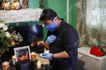 Miguel Hernandez Gomez, cousin of Raul Luis Lopez who died from COVID-19 a month earlier, holds a crucifix and gestures the sign of the cross after the Rev. Fabian Arias performed an in-home service beside Lopez's remains, in the Corona neighborhood of the Queens borough of New York