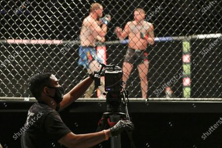 Stock Photo of Videographer focuses on a fight between Donald Cerrone, back left, and Anthony Pettis during a UFC 249 mixed martial arts bout, in Jacksonville, Fla