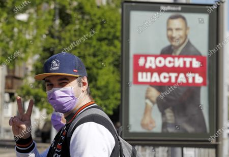 A man wearing a face mask as a preventive measure shows victory sign as he walks past a billboard with a photo of Vitali Klitschko, former heavyweight champion and now Kyiv Mayor written on Stop hanging around calling people to stay at home to protect themselves against the coronavirus. As on May 09, 2020 Ukraine's Health Ministry recorded in total 14,710 confirmed cases and 376 deaths since the beginning of the Coronavirus Covid-19 outbreak. Cabinet of Ministers of Ukraine have extended the coronavirus related quarantine in the country until 22 May 2020, but from May 11, some quarantine restrictions are planned to be relaxed.