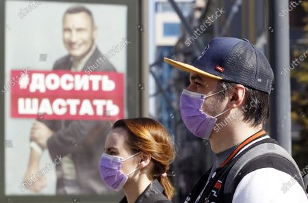 People wearing face masks as a preventive measure walk past a billboard with a photo of Vitali Klitschko, former heavyweight champion and now Kyiv Mayor written on Stop hanging around calling people to stay at home to protect themselves against the coronavirus. As on May 09, 2020 Ukraine's Health Ministry recorded in total 14,710 confirmed cases and 376 deaths since the beginning of the Coronavirus Covid-19 outbreak. Cabinet of Ministers of Ukraine have extended the coronavirus related quarantine in the country until 22 May 2020, but from May 11, some quarantine restrictions are planned to be relaxed.