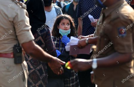 Stranded Kashmiri girl anxiously looks at officials checking documents as she waits with elders to board a bus to a special train home during a lockdown to curb the spread of new coronavirus, in Bangalore, India, . India's lockdown entered a sixth week on Sunday, though some restrictions have been eased for self-employed people unable to access government support to return to work