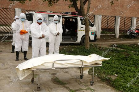 Bangladeshi volunteers wearing protective suits offer funeral prayer next to body of a person who died of Covid-19 at Rayer Bazar graveyard in Dhaka, Bangladesh, 10 May 2020. Countries around the world are taking increased measures to stem the widespread of the SARS-CoV-2 coronavirus which causes the COVID-19 disease.