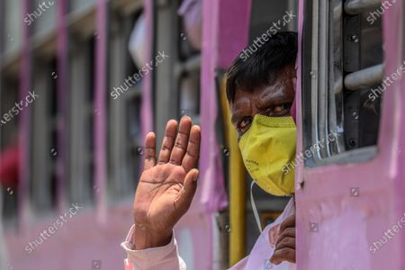 An Indian migrant laborer waves from the bus organised by Brihanmumbai Municipal Corporation to the policemen as he leaves for the Lokmanya Tilak Terminus to catch the train for Patna, to reach for their villages, in Mumbai, India, 10 May 2020. The Indian government announced lockdown extension for two weeks until May 17 with new relaxation action plan for Red, Orange and Green Zones but people still seeking clarity from local authorities as the third phase of the countrywide lockdown begins to stem the widespread of the SARS-CoV-2 coronavirus.