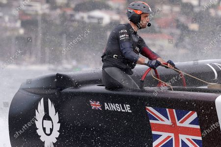 Skipper Ben Ainslie steers the boat as the British team crosses the finish line in the second fleet race of the SailGP series in Sydney. America's Cup teams are returning to the water in varying degrees nearly two months after the coronavirus pandemic forced the shutdown of what would have been an impressive global road show