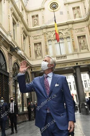 King Philippe - Filip of Belgium (wearing a mask) waves to people at the windows of apartments inside the galery during a royal visit to several shops on and near the Grasmarkt - Marche aux Herbes, in the city center of Brussels, Sunday 10 May 2020. These shops were severely touched by the lockdown measures taken to prevent the spreading of the Corona Virus. As from Monday 11 May, Belgium enters a new phase in the Exit Strategy. All shops can reopen, taking into account several safety measures, for example regarding social distancing.