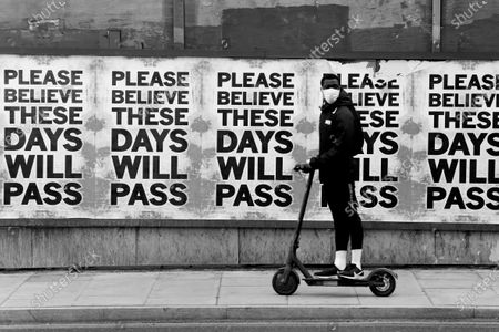 A man rides past a sign of hope during the Covid-19 outbreak, Dalston Junction, London. 'These days will pass'