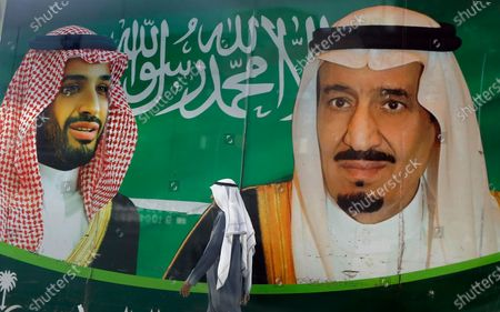 Stock Image of A man walks past a banner showing Saudi King Salman, right, and his Crown Prince Mohammed bin Salman, outside a mall in Jiddah, Saudi Arabia. Saudi Arabia announced, it is tripling taxes on basic goods to 15% and will cut spending on major projects by around $26 billion as it grapples with blows from the coronavirus pandemic and low oil prices on its economy