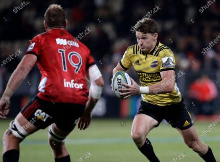 Stock Image of Hurricanes Beauden Barrett, right, runs at Crusaders Luke Romano during the Super Rugby semifinal between the Crusaders and the Hurricanes in Christchurch, New Zealand, Saturday. A domestic tournament involving New Zealand's five Super Rugby teams will begin in mid-June after the New Zealand government Monday, May 11, 2020, loosened restrictions on sporting competitions, imposed because of the coronavirus pandemic