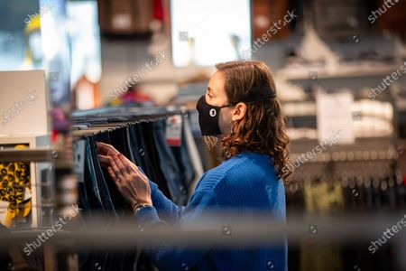 Illustration picture shows a shop assistant wearing a mouth maks, during a visit of Minister Muylle to clothes shops Boggie and Brooklyn, in the city center of Roeselare, Monday 11 May 2020. Belgium goes into its ninth week of confinement. Stage 1B of the deconfinement plan in the ongoing corona virus crisis starts. All shops can reopen and more people can return to work.
