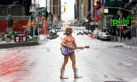 A busker named Robert Burck, known as the Naked Cowboy, stands in the middle of a quiet Times Square in New York, New York, USA, 11 May 2020.