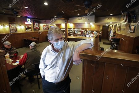 Scott Barnes, owner of The Friendly Tavern, talks with a customer as they leave, in Zionsville, Ind. Dine-in restaurants in most Indiana counties were allowed to open at 50 percent capacity