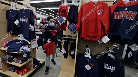 Ivy Lee restocks and reorganizes merchandise at Rally House, in Mayfield Heights, Ohio. Ohio's retail stores can re-open Tuesday following the states guidelines for social distancing