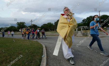 Using social distancing due to the COVID-19 pandemic, the Rev. Pat O'Brien, of St.Pius X Catholic Church, carries a monstrance as he leads a Eucharistic procession through a neighborhood near his church in San Antonio, . San Antonio's Archbishop today announced that parishes can open their doors next Tuesday for daily services, allowing for weekend Masses to begin May 23 and 24