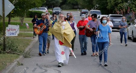 Using social distancing due to the COVID-19 pandemic, the Rev. Pat O'Brien of St. Pius X Catholic Church leads a Eucharistic procession through a neighborhood near his church in San Antonio, . San Antonio's archbishop on Monday announced that parishes can open their doors Tuesday of next week for daily services, allowing for weekend Masses to begin May 23 and 24