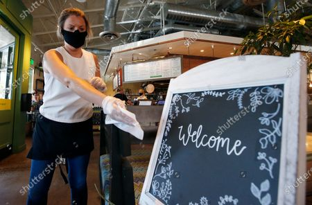 Stock Photo of Laura Spencer, a recruiter at the corporate offices of the Fox Restaurant Concepts' Phoenix-based eateries, cleans off surfaces as she helps out at Flower Child restaurant as the restaurant is just one of the gradually opening full service dine-in establishments, expanding from their takeout option, to reopen as Arizona slowly relaxes restrictions due to the coronavirus, in Phoenix