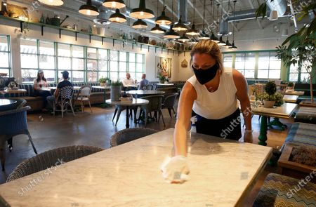 Laura Spencer, a recruiter at the corporate offices of the Fox Restaurant Concepts' Phoenix-based eateries, cleans off a dining table as she helps out at Flower Child restaurant as the restaurant is just one of the gradually opening full service dine-in establishments, expanding from their takeout option, to reopen as Arizona slowly relaxes restrictions due to the coronavirus, in Phoenix