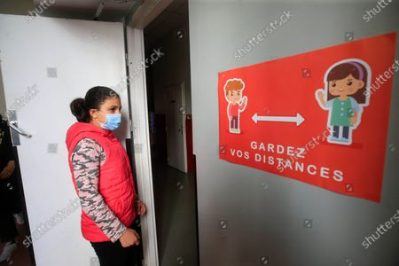 """A sign reading """"keep social distances"""" is seen inside the Simone Veil Primary School in Nice, France, May 12, 2020. Nearly two months after ordering its 67 million population to stay home to stem the coronavirus outbreak, France on Monday cautiously started a gradual process to return to normalcy, easing some restrictions while maintaining others to avoid a new epidemic wave. Some 1.5 million children, or 22 percent of the country's total number of pupils, are preparing to go to school on Tuesday, and 190,000 teachers resumed work on Monday, according to the Education Ministry's data."""