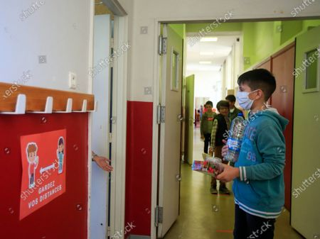 Schoolchildren wearing face masks line up as they enter the classroom at the Simone Veil Primary School in Nice, France, May 12, 2020. Nearly two months after ordering its 67 million population to stay home to stem the coronavirus outbreak, France on Monday cautiously started a gradual process to return to normalcy, easing some restrictions while maintaining others to avoid a new epidemic wave. Some 1.5 million children, or 22 percent of the country's total number of pupils, are preparing to go to school on Tuesday, and 190,000 teachers resumed work on Monday, according to the Education Ministry's data.