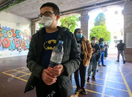 Schoolchildren wearing face masks line up as they enter the Simone Veil Primary School in Nice, France, May 12, 2020. Nearly two months after ordering its 67 million population to stay home to stem the coronavirus outbreak, France on Monday cautiously started a gradual process to return to normalcy, easing some restrictions while maintaining others to avoid a new epidemic wave. Some 1.5 million children, or 22 percent of the country's total number of pupils, are preparing to go to school on Tuesday, and 190,000 teachers resumed work on Monday, according to the Education Ministry's data.