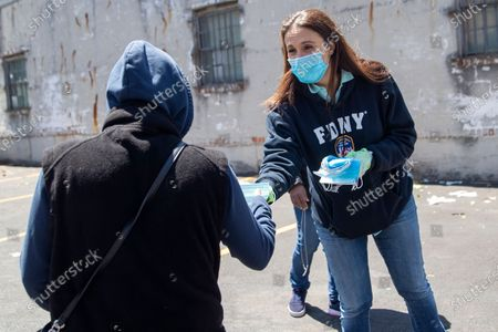 Democratic New York 14th Congressional District candidate Michelle Caruso-Cabrera, right, distributes masks at the St. Mark AME Church - The Voices of Hagar food pantry during the coronavirus pandemic, in the Flushing neighborhood of the Queens borough of New York