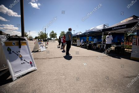 A sign asks voters to keep their distances as they arrive to cast their ballots at a in-person polling center on the Lancaster National Soccer Center's parking lot during the Congressional 25th District Special General Election amid the coronavirus pandemic in Lancaster, California, USA, 12 May 2020. The election, following Democrat Katie Hill's resignation, opposes Democratic candidate Christy Smith and Republican candidate Mike Garcia. US President Donald Trump accused Democrats of trying to 'steal' these special election in California by adding this polling place in Lancaster, one of the most diverse sections of the district.