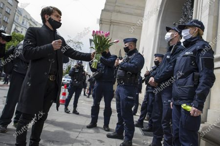 """Michal tries to give flowers to a policewoman guarding the entrance to the Ministry of Agriculture during the campaign. Leader of Agro Union organization (Agro Unia), Michal Kolodziejczak, came to Warsaw - as he claimed: """"to thank the minister for burying Polish agriculture and selling it to corporations"""". According to the organization, the Minister of Agriculture, Jan Krzysztof Ardanowski led many family farms to the brink of bankruptcy, deepened the stereotypical divisions between the villages and the city, and allowed foreign corporations to dominate in the food production and trade market. Kolodziejczak noted that unlike Poland, in the era of coronavirus, governments of other countries are trying to save the agricultural sector."""