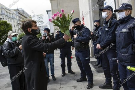 """Stock Picture of Michal tries to give flowers to a policewoman guarding the entrance to the Ministry of Agriculture during the campaign. Leader of Agro Union organization (Agro Unia), Michal Kolodziejczak, came to Warsaw - as he claimed: """"to thank the minister for burying Polish agriculture and selling it to corporations"""". According to the organization, the Minister of Agriculture, Jan Krzysztof Ardanowski led many family farms to the brink of bankruptcy, deepened the stereotypical divisions between the villages and the city, and allowed foreign corporations to dominate in the food production and trade market. Kolodziejczak noted that unlike Poland, in the era of coronavirus, governments of other countries are trying to save the agricultural sector."""