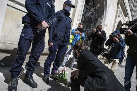 """Stock Photo of Michal kneeling and putting flowers next to the feet of a policewoman guarding the entrance to the Ministry of Agriculture during the campaign. Leader of Agro Union organization (Agro Unia), Michal Kolodziejczak, came to Warsaw - as he claimed: """"to thank the minister for burying Polish agriculture and selling it to corporations"""". According to the organization, the Minister of Agriculture, Jan Krzysztof Ardanowski led many family farms to the brink of bankruptcy, deepened the stereotypical divisions between the villages and the city, and allowed foreign corporations to dominate in the food production and trade market. Kolodziejczak noted that unlike Poland, in the era of coronavirus, governments of other countries are trying to save the agricultural sector."""