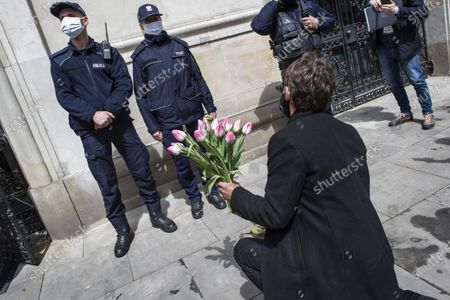 """Stock Image of Michal kneeling and putting flowers next to the feet of a policewoman guarding the entrance to the Ministry of Agriculture during the campaign. Leader of Agro Union organization (Agro Unia), Michal Kolodziejczak, came to Warsaw - as he claimed: """"to thank the minister for burying Polish agriculture and selling it to corporations"""". According to the organization, the Minister of Agriculture, Jan Krzysztof Ardanowski led many family farms to the brink of bankruptcy, deepened the stereotypical divisions between the villages and the city, and allowed foreign corporations to dominate in the food production and trade market. Kolodziejczak noted that unlike Poland, in the era of coronavirus, governments of other countries are trying to save the agricultural sector."""