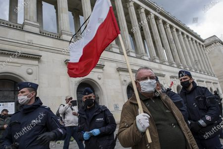 """A farmer with Michal holds the Polish flag outside the Ministry of Agriculture during the campaign. Leader of Agro Union organization (Agro Unia), Michal Kolodziejczak, came to Warsaw - as he claimed: """"to thank the minister for burying Polish agriculture and selling it to corporations"""". According to the organization, the Minister of Agriculture, Jan Krzysztof Ardanowski led many family farms to the brink of bankruptcy, deepened the stereotypical divisions between the villages and the city, and allowed foreign corporations to dominate in the food production and trade market. Kolodziejczak noted that unlike Poland, in the era of coronavirus, governments of other countries are trying to save the agricultural sector."""