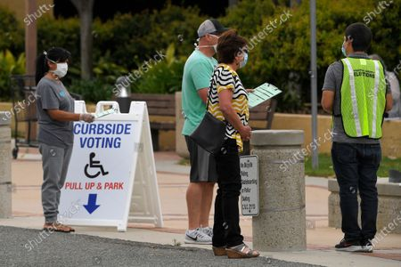 Voting official helps walk-up voters in a special election for California's 25th Congressional District during the coronavirus outbreak, in Simi Valley, Calif. Republican Mike Garcia and Democrat Christy Smith are running for the seat after the resignation of Rep. Katie Hill, D-Calif