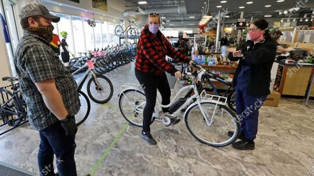 Stock Photo of Store manager Josh Hayden, left to right, talks with Kay Amey and Jackie Gee about a new bicycle at Eddy's Bike Shop, in Willoughby Hills, Ohio. Ohio retail businesses were set to reopen Tuesday following a nearly two-month-long shutdown ordered by Gov. Mike DeWine to limit the spread of the new coronavirus