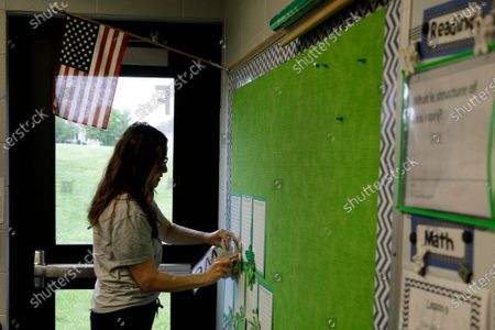 Stock Image of Teacher Betsy Adams removes students work from a St. Patrick's Day bulletin board as she packs items in her 3rd grade classroom at Walnut Grove Elementary School, in Olathe, Kan. Teachers were gathering belongings and classwork of their students so they could be picked up by parents next week. The school closed on March 13 as all Kansas schools were ordered shut to help prevent the spread of the coronavirus and eventually ordered closed for the remainder of the school year